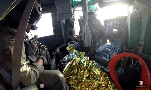 I due migranti salvati a bordo elicottero si tengono per mano
