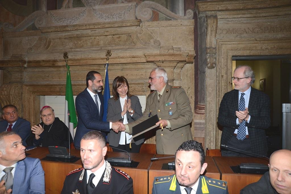 Foto n 1 il Sindaco Avv Leonardo LATINI consegna la pergamena al Direttore del Polo di mantenimento delle Armi leggere Colonnello DEI BARDI